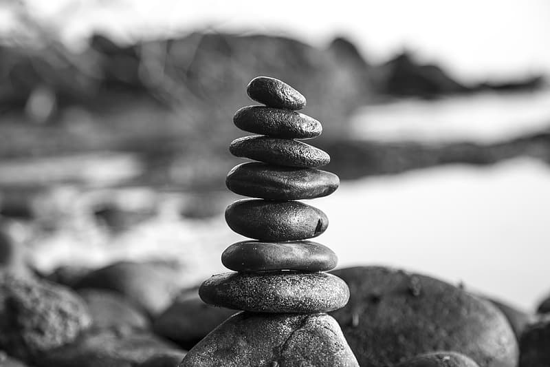 Grayscale photo of stones stacked together