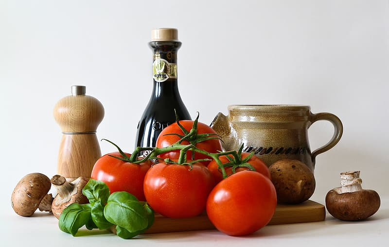 Red tomatoes beside brown ceramic jar