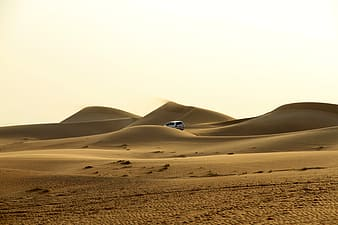 White vehicle traveling at desert