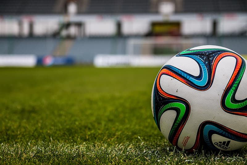 White and green soccer ball on green grass field