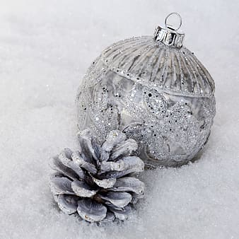 Silver glitter bauble and white painted pine cone on fur textile