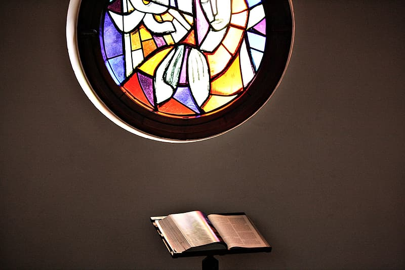 Opened book near multicolored stained glass window