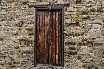 Brown wooden door on white brick wall