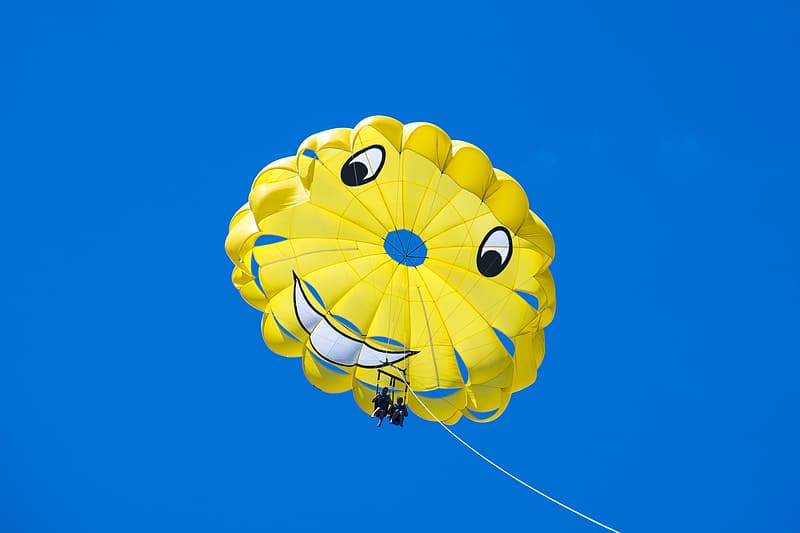 Man riding yellow happy face parachute during blue sky