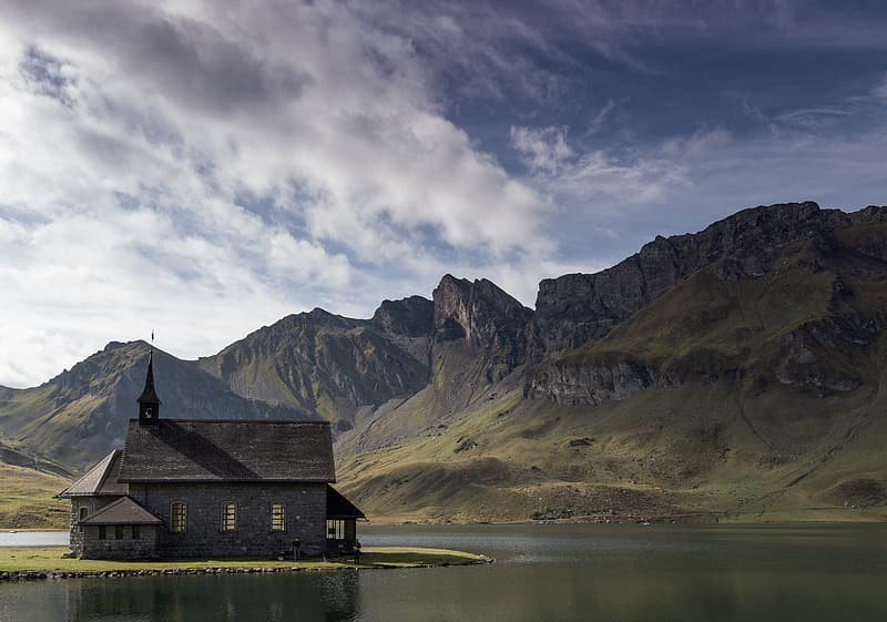 Brown wooden house on lake near mountain under white clouds and blue sky during daytime
