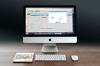Silver iMac, Apple Magic Mouse, Apple Wireless Keyboard and white iPad on brown desk