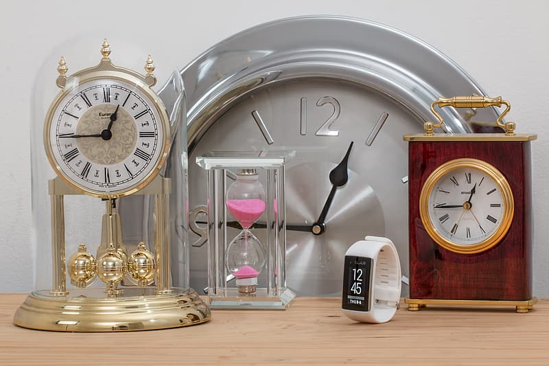 Gold anniversary clock with hour glass and roman analog table clock on brown wooden table