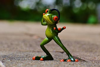 Selective focus photography of red and green frog wearing headset figurine on brown surface