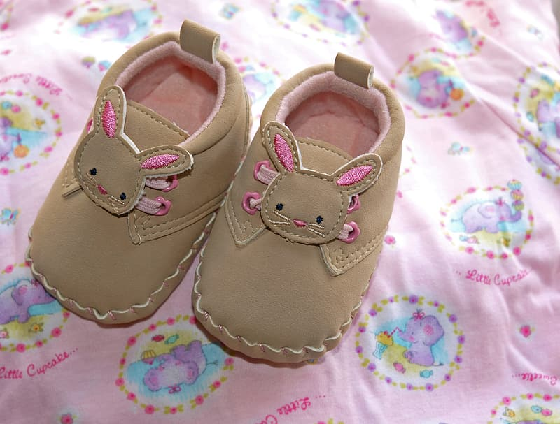 Pair of infant's brown-and-pink leather crib shoes on pink and multicolored textile