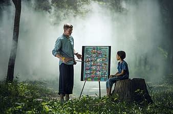 Person holding a stick pointing an Alphabet chart and child sitting looking on the chart