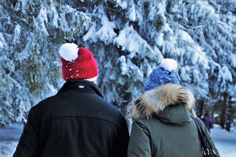 Person in black jacket and red and white knit cap standing near snow covered trees during