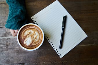 Photo of black pen on white spring note book near cup of cappuccino