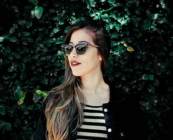Woman in black and white striped shirt wearing sunglasses standing beside green leaves