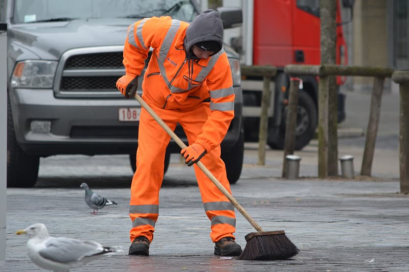 Man sweeping the road near pigeons and vehicle