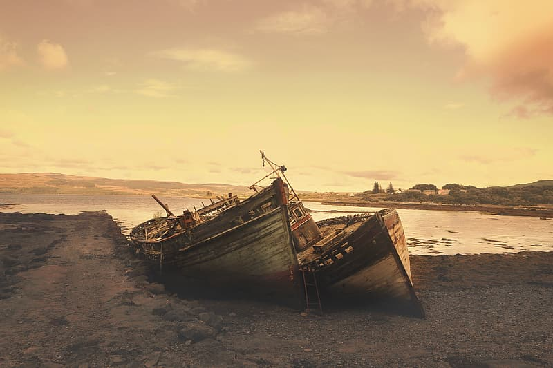 Two brown boats on seashore at golden hour