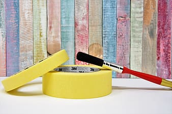 Red handle brush beside yellow round plastic container