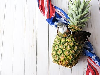 Green and yellow pineapple fruit on blue and red scarf