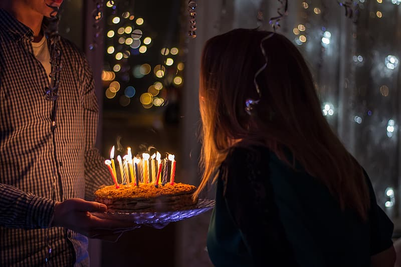 Man holding cake with candle in front of woman