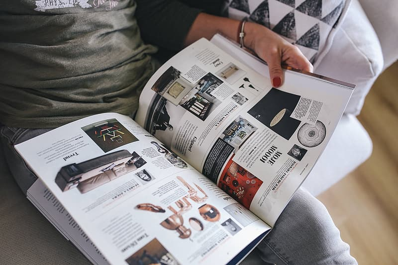 Person holding white and black magazine