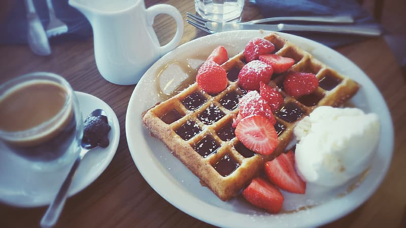 Waffles and sliced strawberries on top of plate