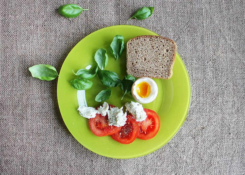 Slice tomato with egg and bread on green plate