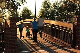 Group of people on brown wooden bridge during sunset