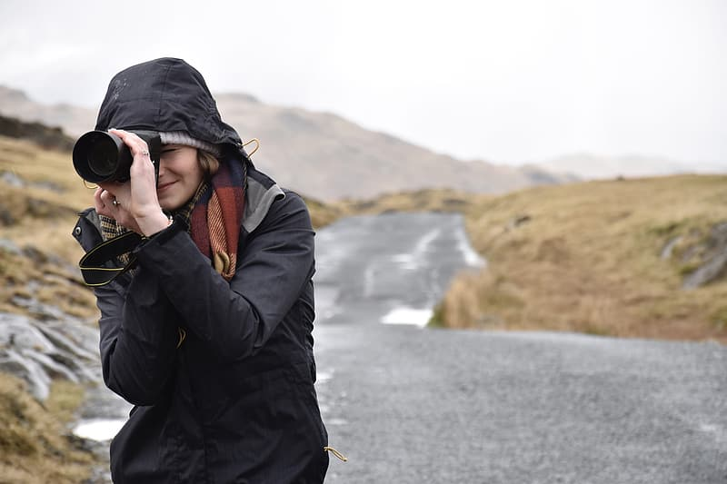 Woman in black hooded jacket and black DSLR camera