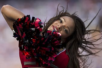 Woman with pom-pom cheering during day