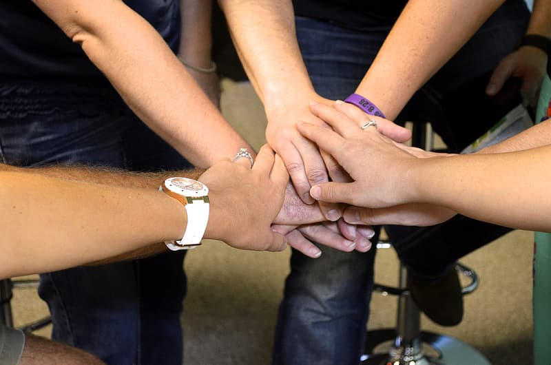 Group of people doing hand sign