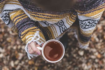 Person in sweater holding a filled mug