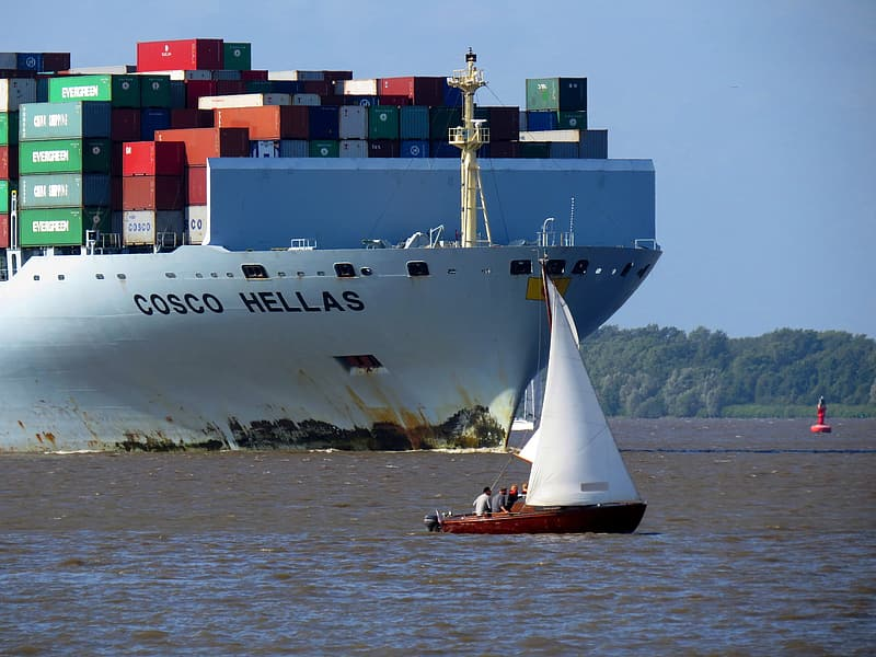 White and red cargo ship on sea during daytime