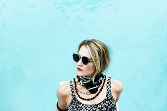 Woman in black and white polka dot tank top wearing sunglasses