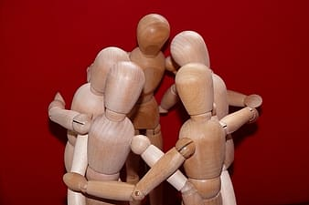 Five brown wooden puppet hugging each other