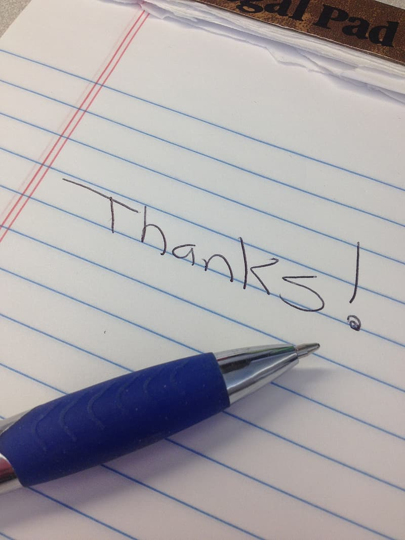 Blue pen on white lined paper with Thanks! written on it