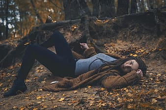 Woman wearing brown cardigan and gray t-shirt with black sweatpants laying in forest during daytime