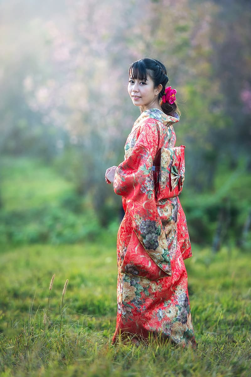 Woman in red and blue floral dress standing on green grass field during daytime