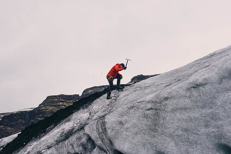 Person in red jacket and black pants standing on gray rock mountain during daytime