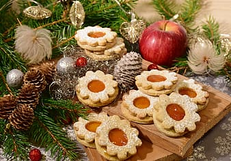 Biscuits in brown wooden tray near ripe apple