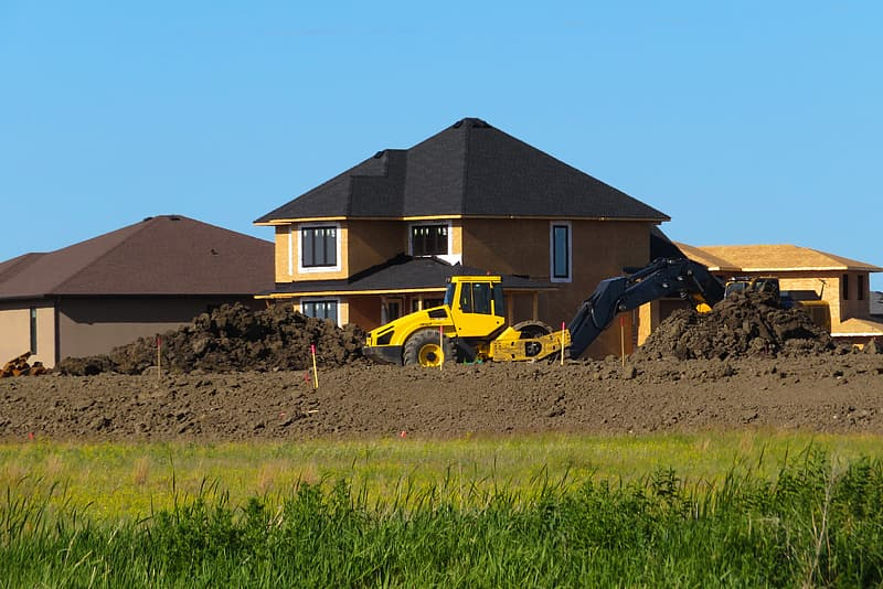 Yellow and black heavy equipment on green grass field during daytime