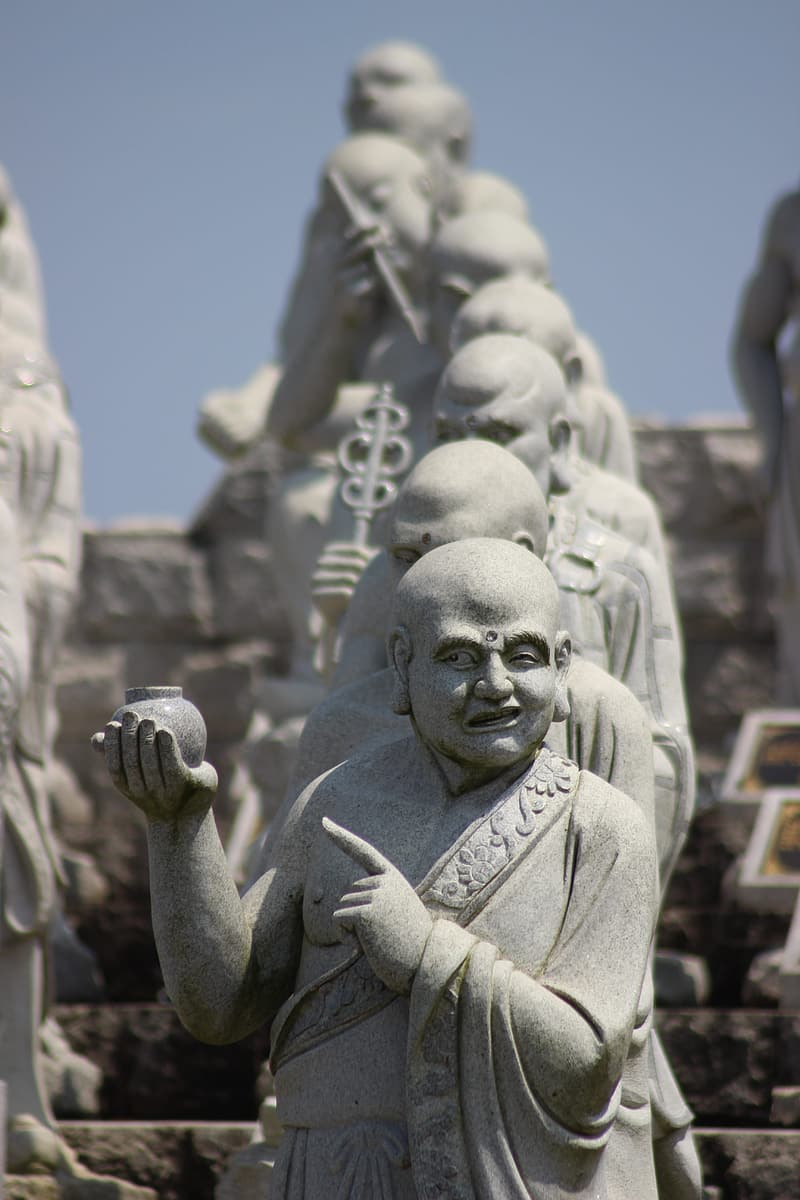 Gray monk pointing finger while holding pot statue
