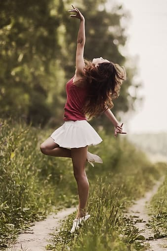 Woman in pink top and white pleated mini skirt doing dance gesture on grass covered pathway