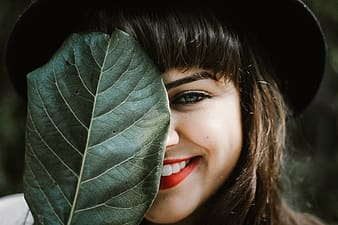 Shallow photography of woman holding leaf