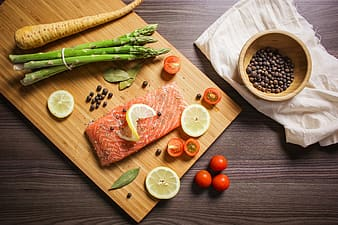 Slice fish with asparagus on brown chopping board