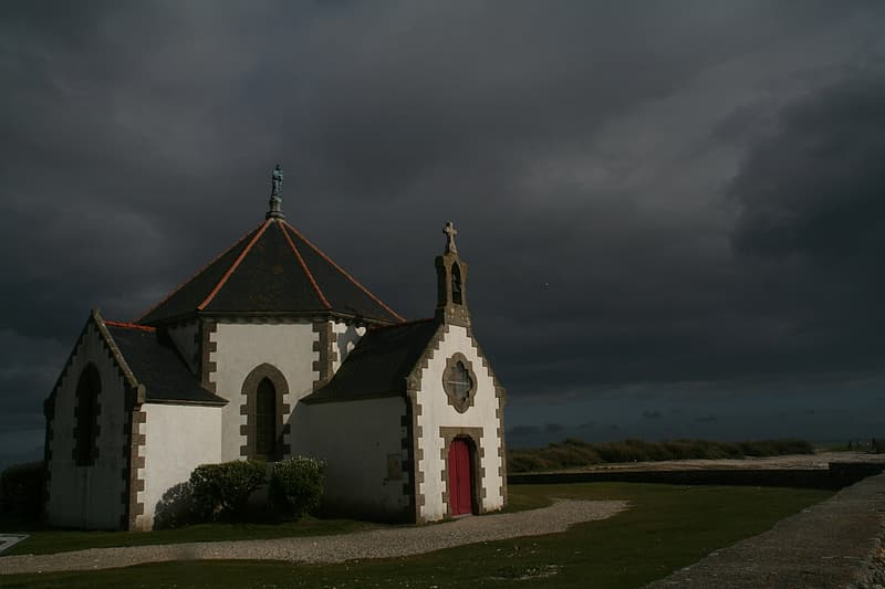 White and red concrete church under gray clouds