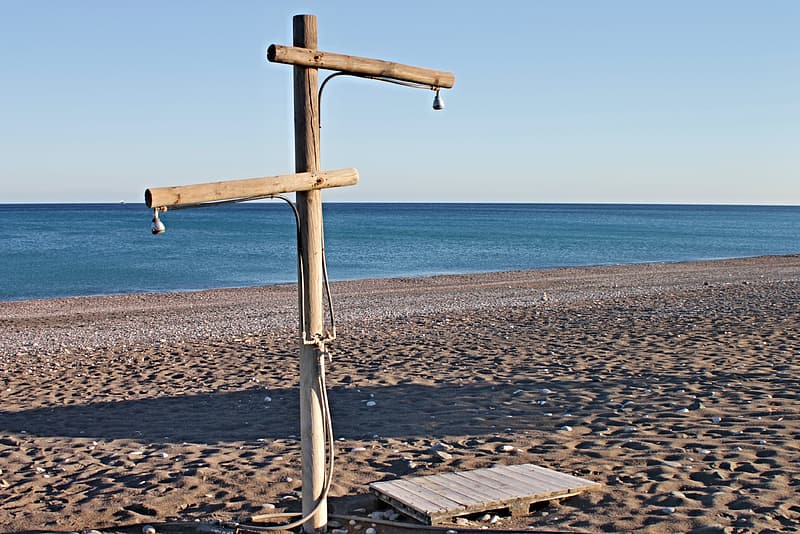 Brown wooden cross on beach during daytime