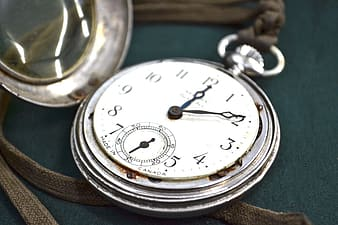 Silver-colored pocket watch at 12:10