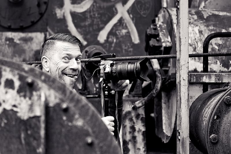 Grayscale photo of man smiling in front of DSLR camera