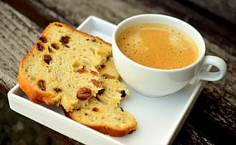 Sliced bread and cup of coffee on white ceramic plate