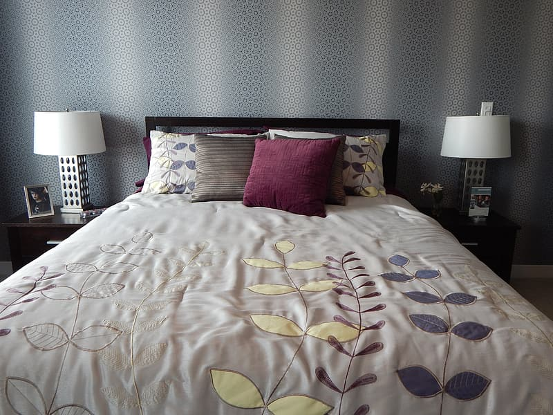 White, yellow, and blue floral bedspread and assorted-color throw pillows