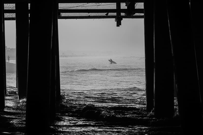 Grayscale photo of a man surfing on sea